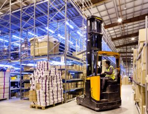 Worker in the motion on forklift in the large modern warehouse